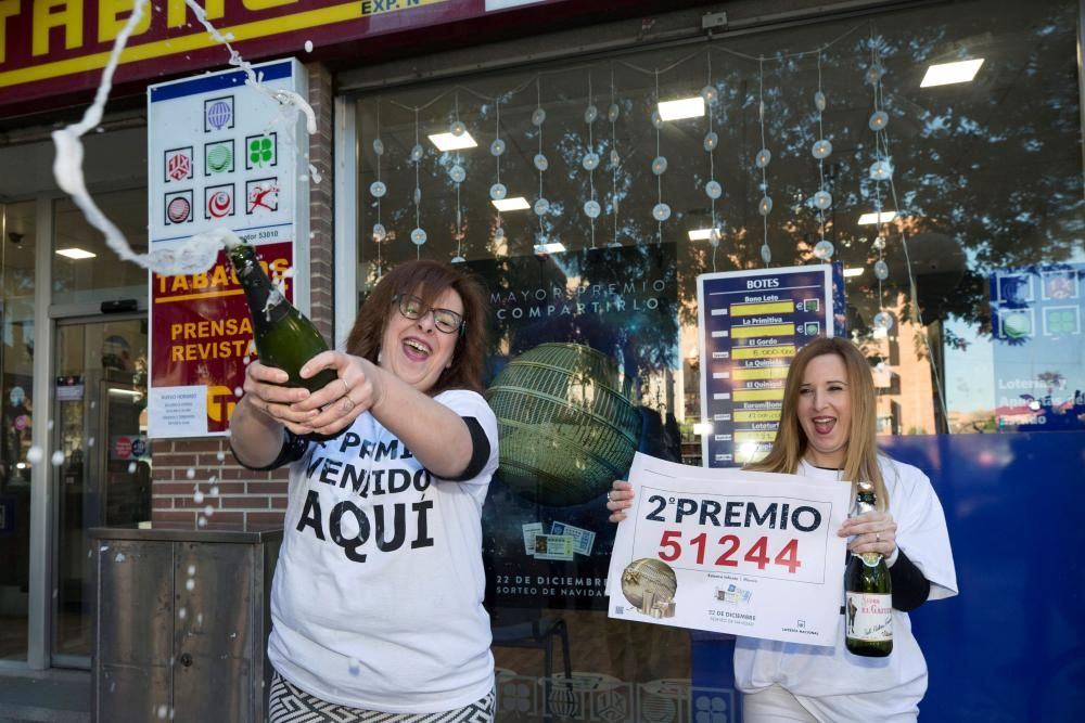 Las empleadas del punto receptor de loterías número 53.010 de la calle Pintor Almela Costa de Murcia, Esther Jaén (i) y Yolanda Leal (d) celebran la venta de un décimo del segundo premio el 51.244 premiado con 125.000 euros. EFE