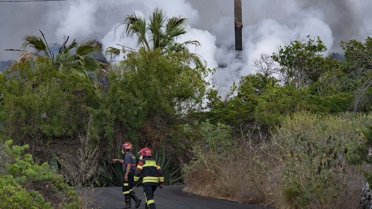 Dos bombers treballen en una de les zones afectades per l'erupció del volcà