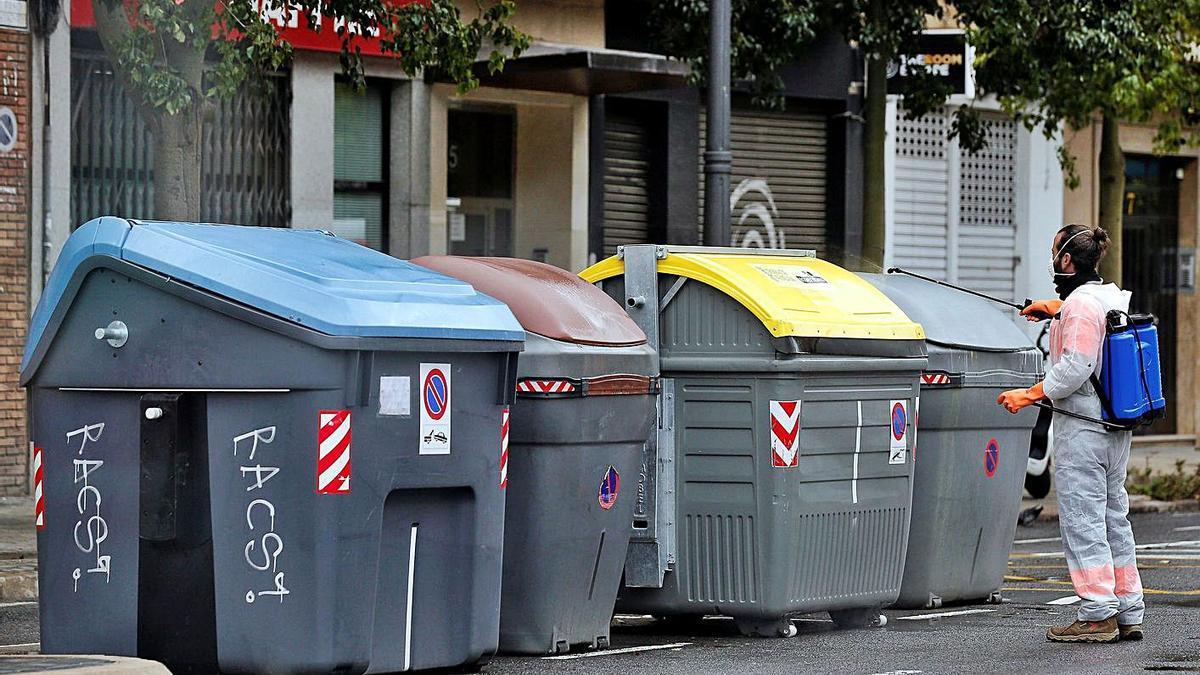Un operari desinfecta els contenidors durant els dies més durs de la pandèmia.   EFE/MANUEL BRUQUE
