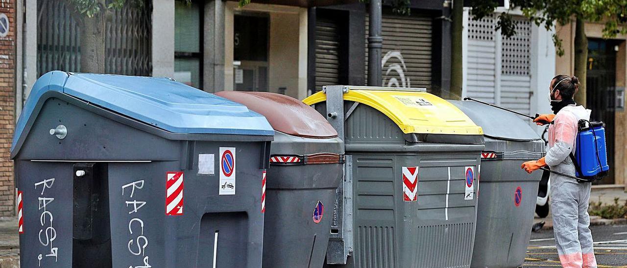 Un operario desinfecta los contenedores durante los días más duros de la pandemia. | EFE/MANUEL BRUQUE