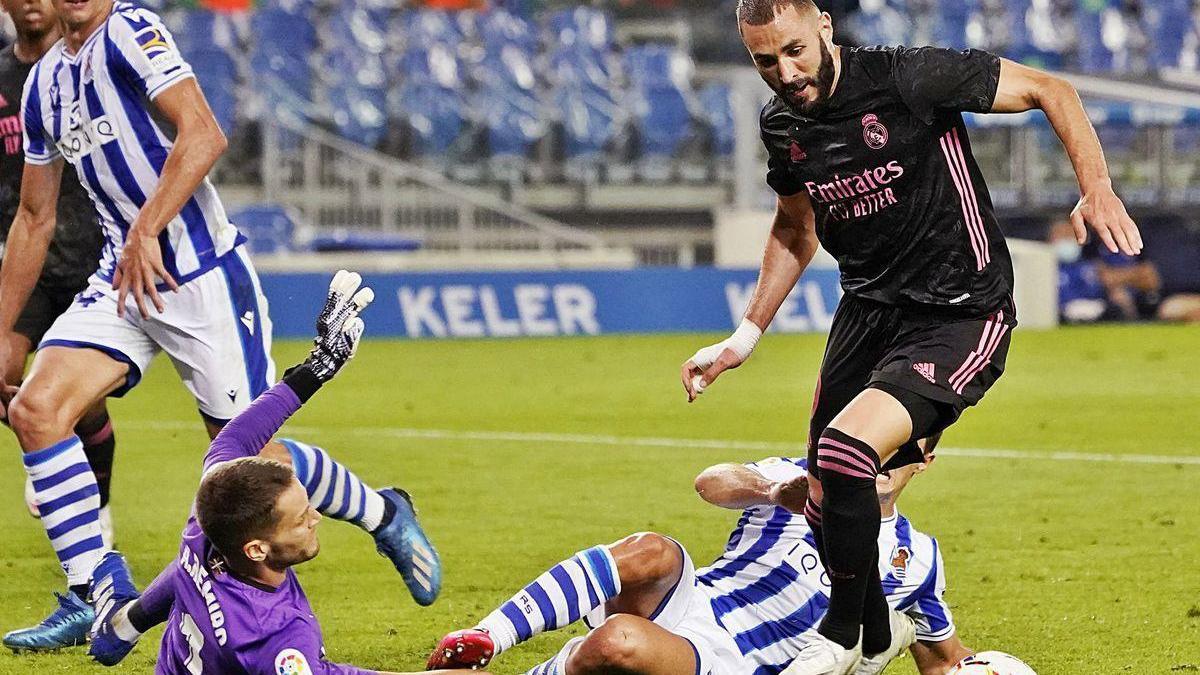 Benzema trata de regatear a Remiro, portero de la Real.