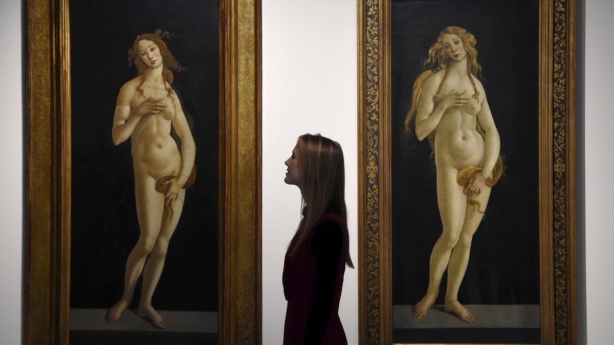 Una mujer posa delante de dos cuadros de Venus de Botticelli que se exponen en el Museo Victoria and Albert de Londres.