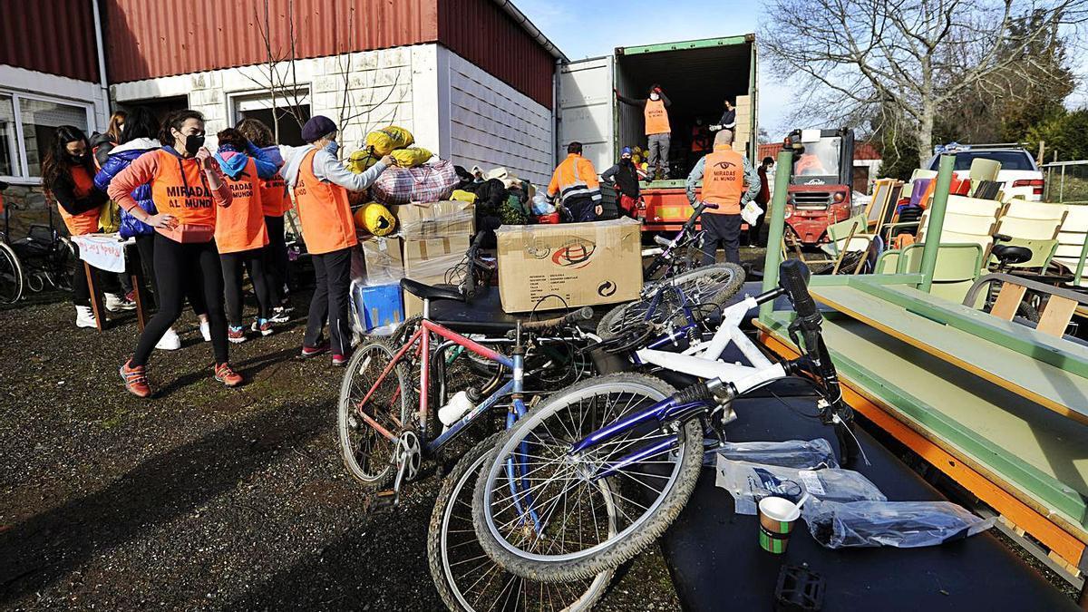 Un grupo de personas voluntarias carga bicicletas y otro material en el contenedor.  | // BERNABÉ/JAVIER LALÍN