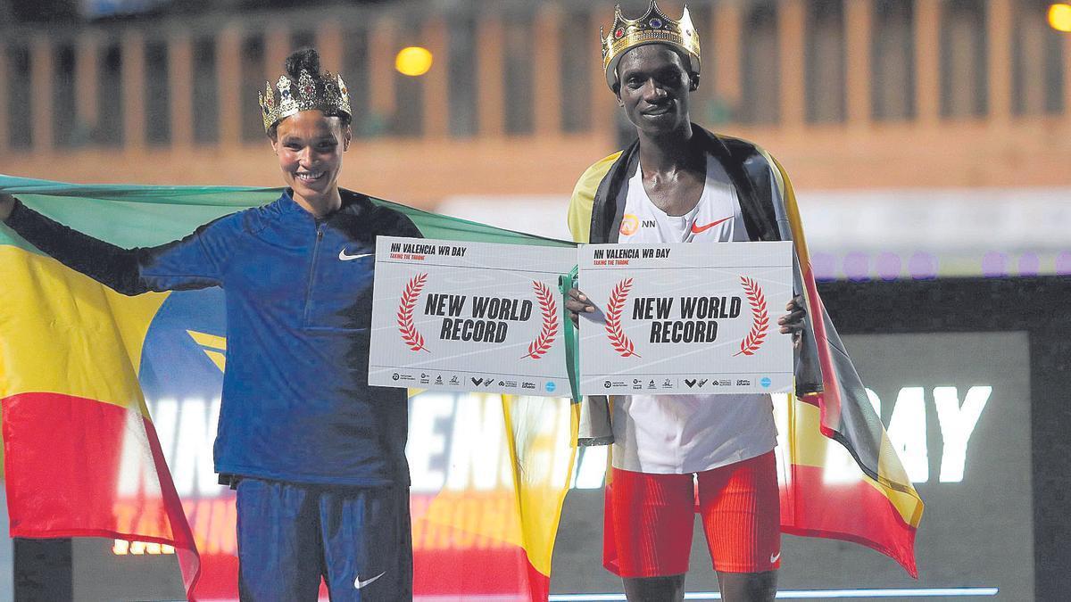 Chepteguei y Gidey posan con los carteles que reflejan sus récords mundiales.