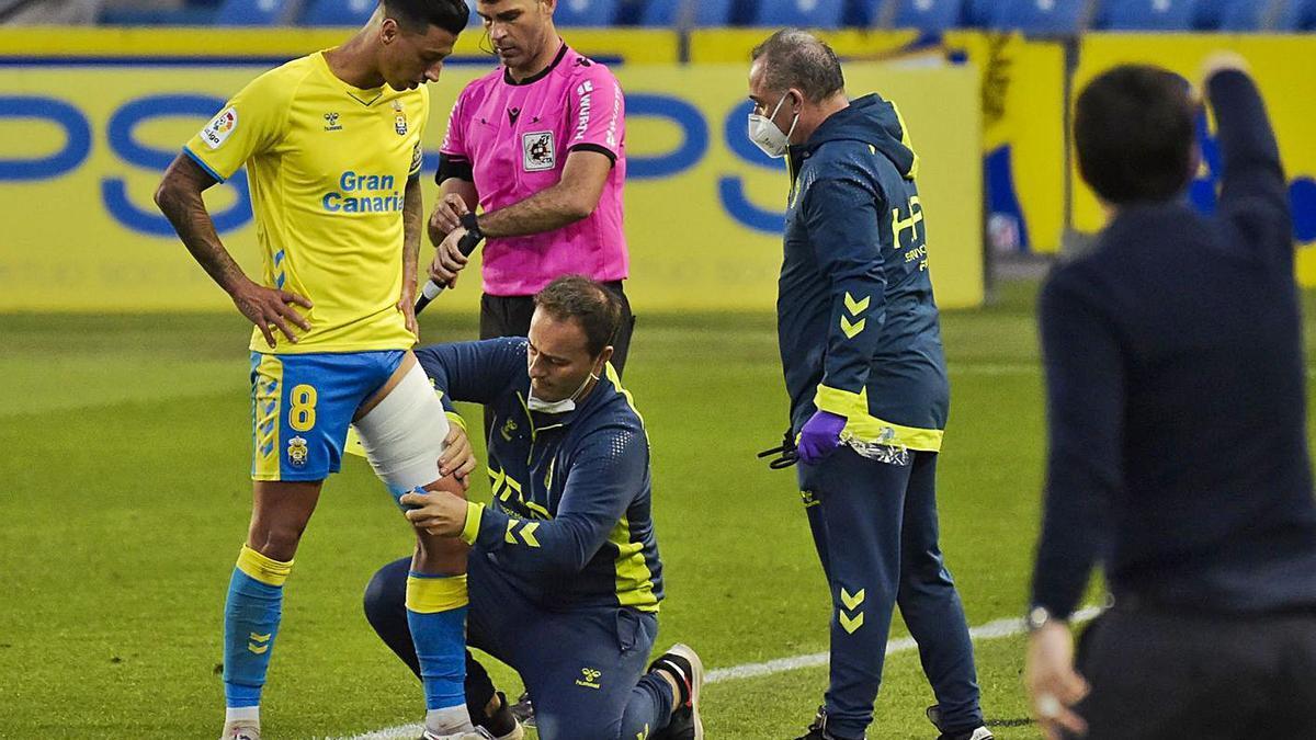 Maikel Mesa, atendido por Juan Naranjo, fisioterapeuta de la UD, tras su lesión frente al Rayo Vallecano. | | ANDRÉS CRUZ