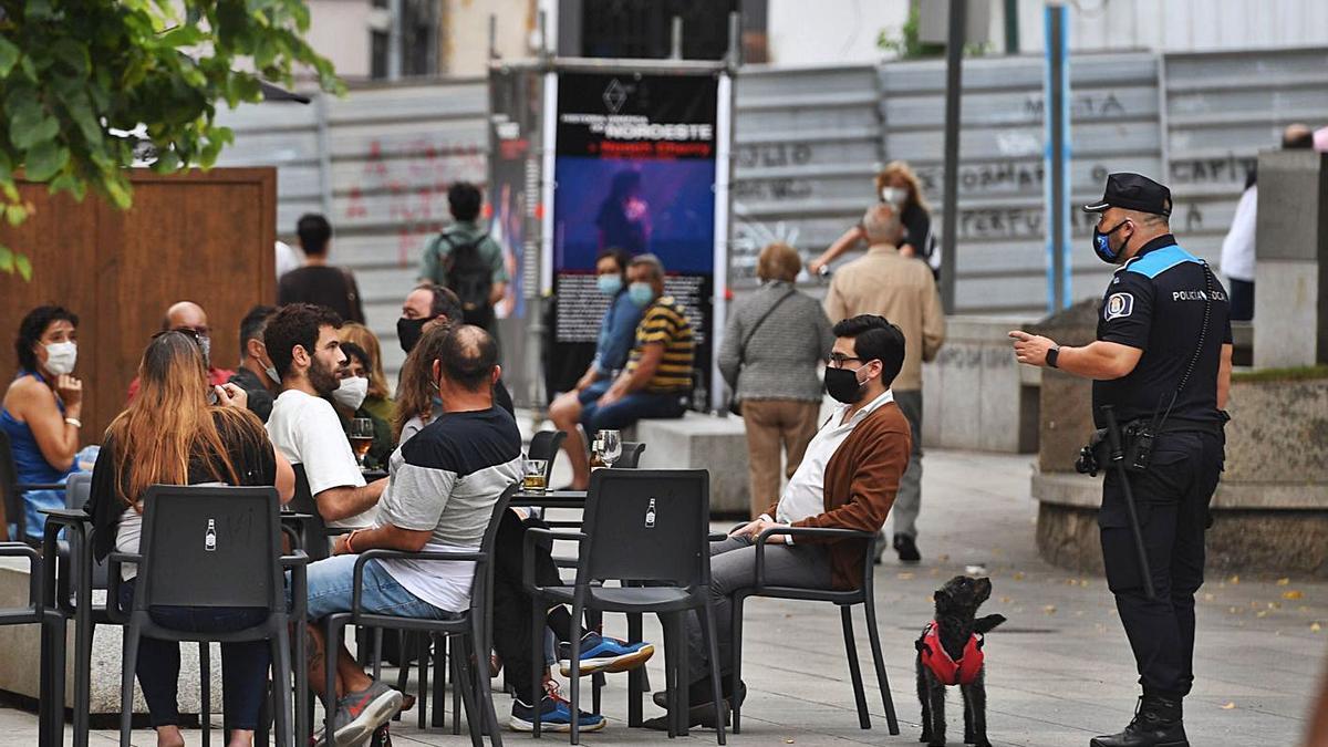 Un agente de la Policía Local, ante clientes de terrazas, en verano.   | // CARLOS PARDELLAS