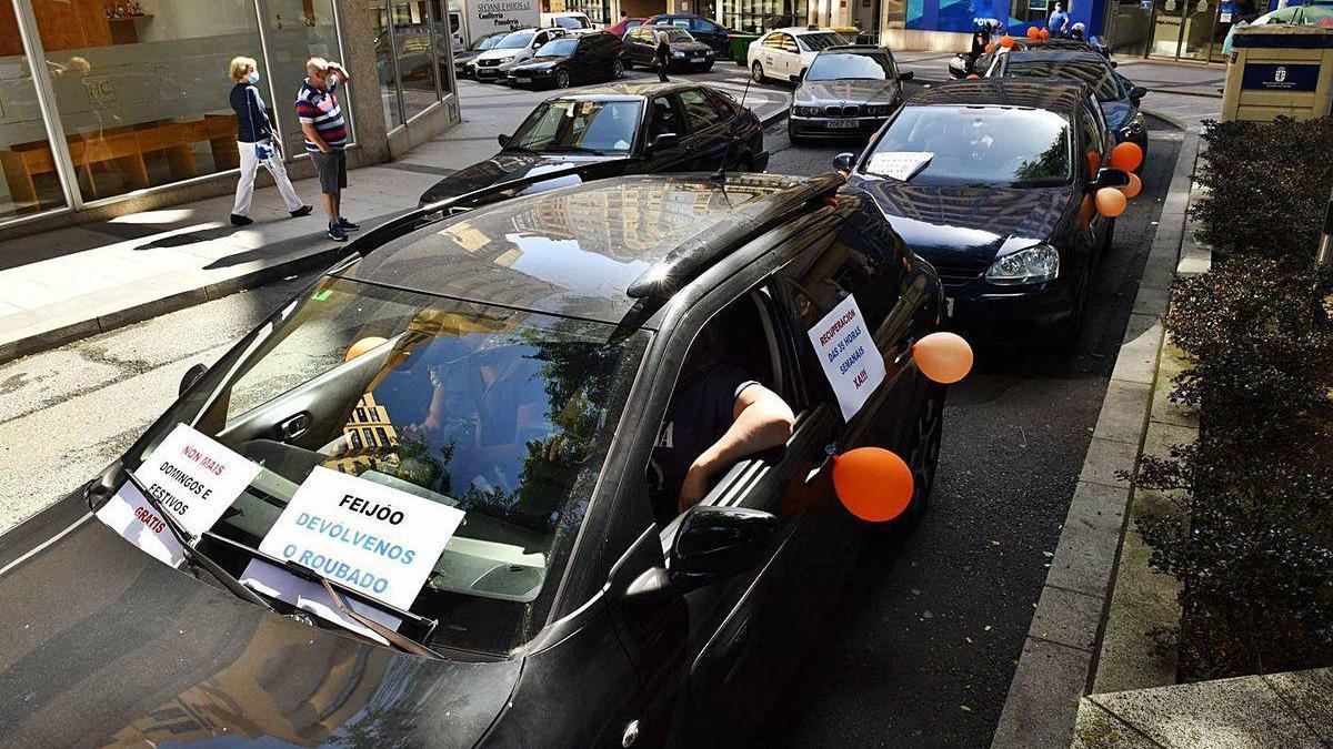 Varios coches protestan por las condiciones del sector, ayer, en A Coruña.