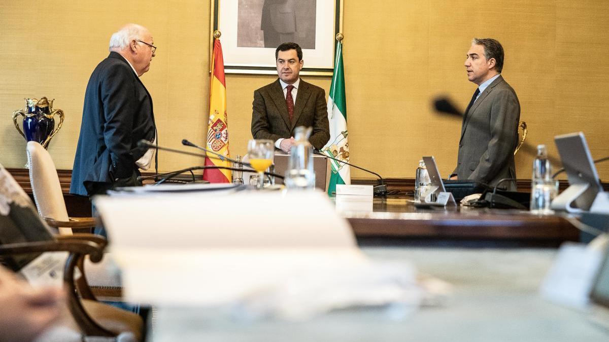 El presidente de la Junta de Andalucía, Juanma Moreno, junto a los consejeros de Salud y Familias, Jesús Aguirre, y de la Presidencia, Elías Bendodo, en una reunión del Consejo de Gobierno.