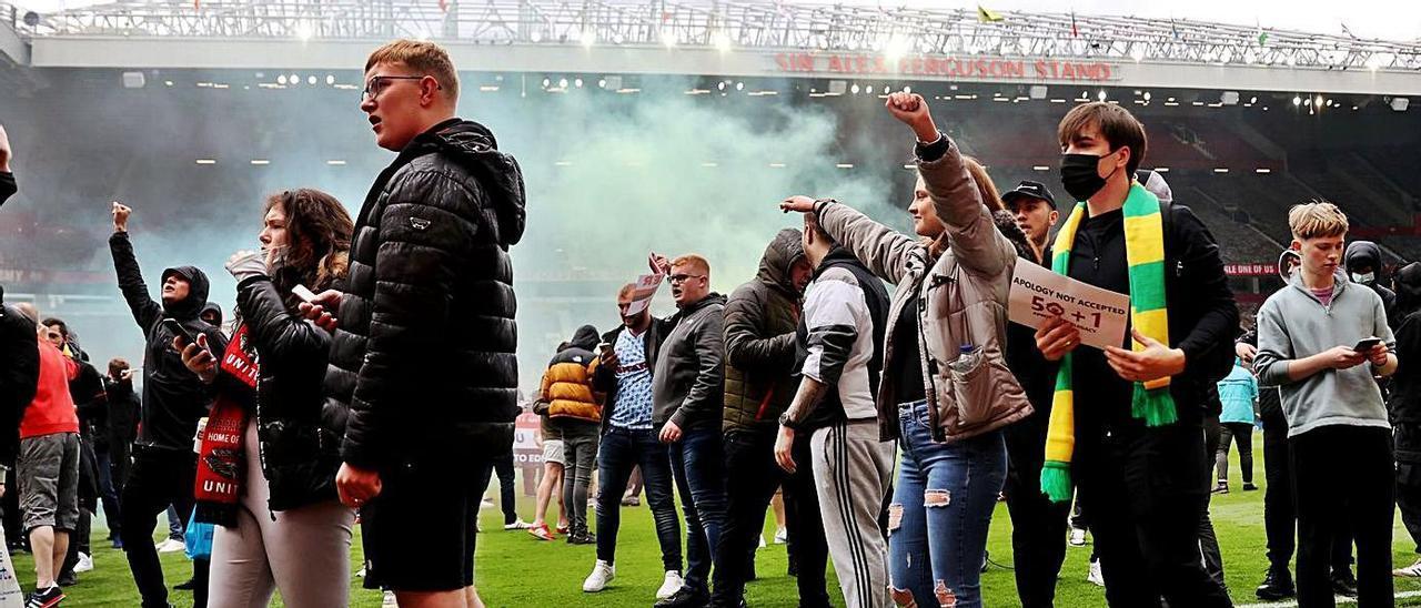 Hinchas del Manchester United, el domingo, en el césped de Old Trafford, con uno de ellos, a la derecha, con un cartel reivindicando la ley del 50+1.