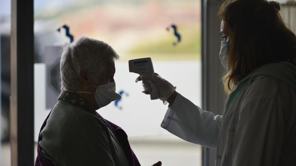 Una sanitaria toma la temperatura a una paciente