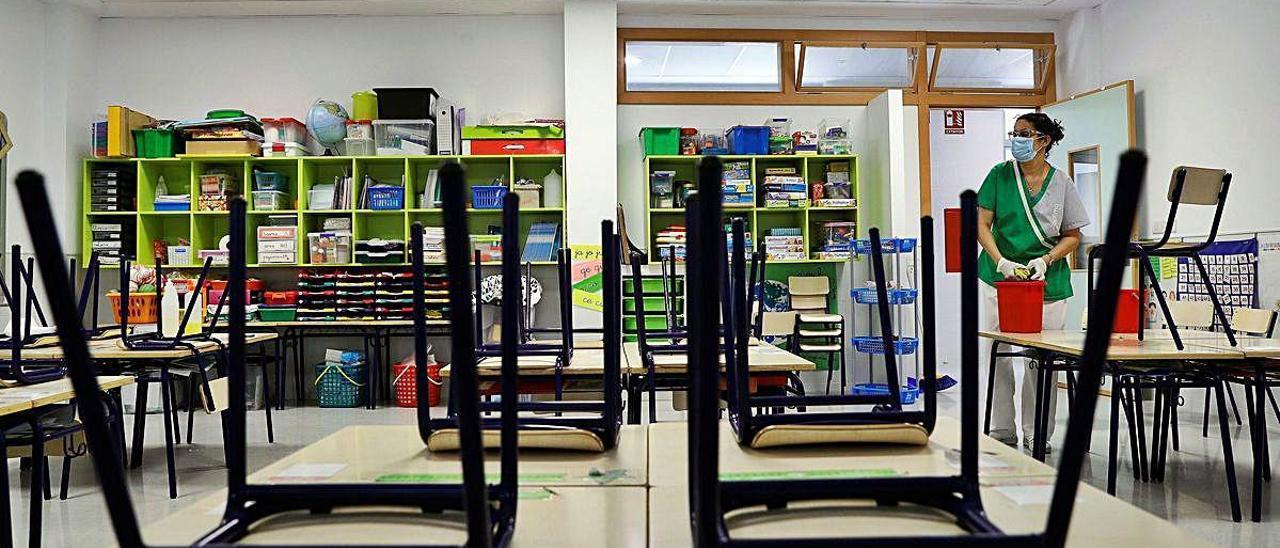 Una trabajadora del servicio de limpieza desinfecta un aula del CEIP 103 de València.