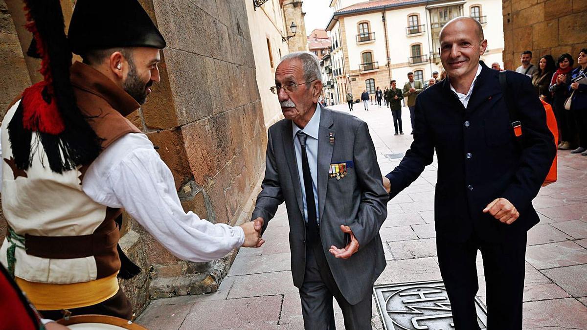 García Riestra, en el centro, acompañado de Xuan Santori, saluda a un gaitero en Oviedo, durante la presentación del libro sobre su experiencia en Buchenwald, publicado originalmente en asturiano en 2018. | L. Murias