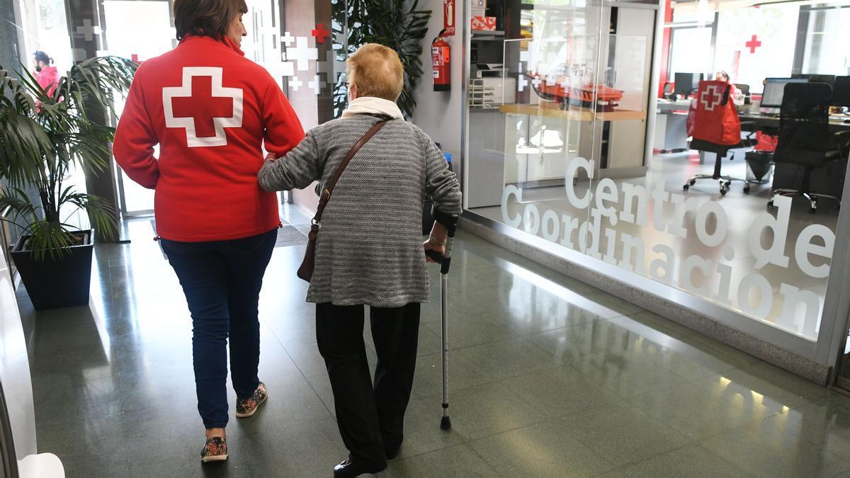 Una voluntaria de Cruz Roja acompaña a una señora mayor.