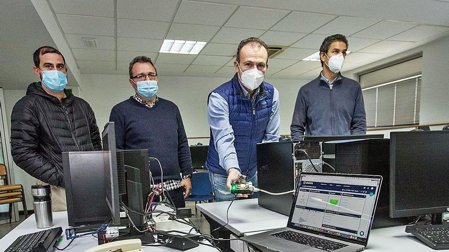 El director de la Escuela Politécnica muestra el sensor de CO2 junto a los investigadores.  | ALEX DOMÍNGUEZ