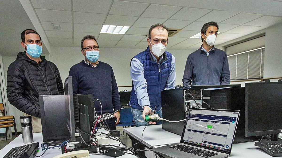 El director de la Escuela Politécnica muestra el sensor de CO2 junto a los investigadores.