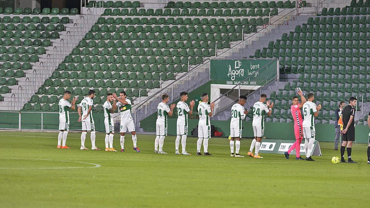 Los jugadores del Elche aplauden a unas gradas vacías antes del partido ante el Valencia.