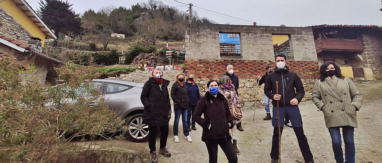 Arriba, vecinos de Piedracea con miembros de Podemos, en el pueblo. A la izquierda, la roca situada sobre el pueblo que amenaza con caer. | A. V.