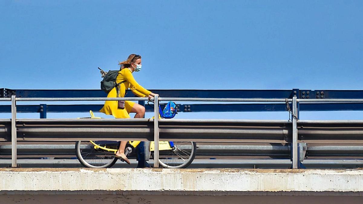 A woman rides a bicycle with a mask on Avenida Martítima in Las Palmas de Gran Canaria.