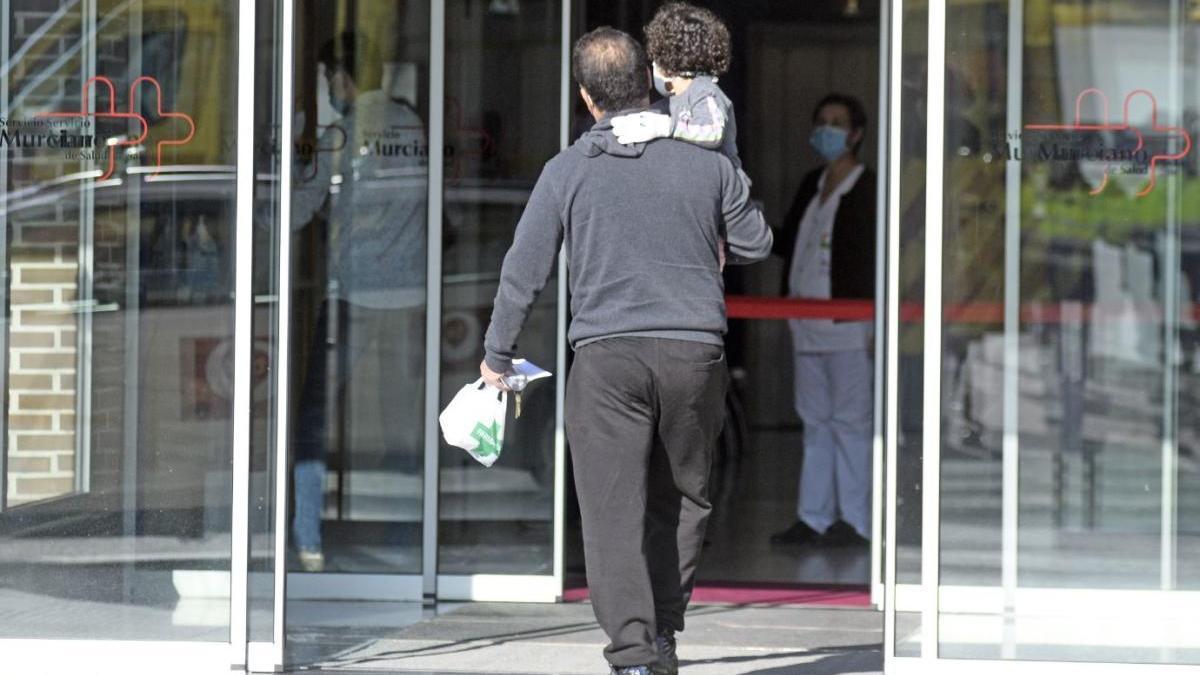 Un hombre con un menor en brazos entra a un centro de salud de Murcia.