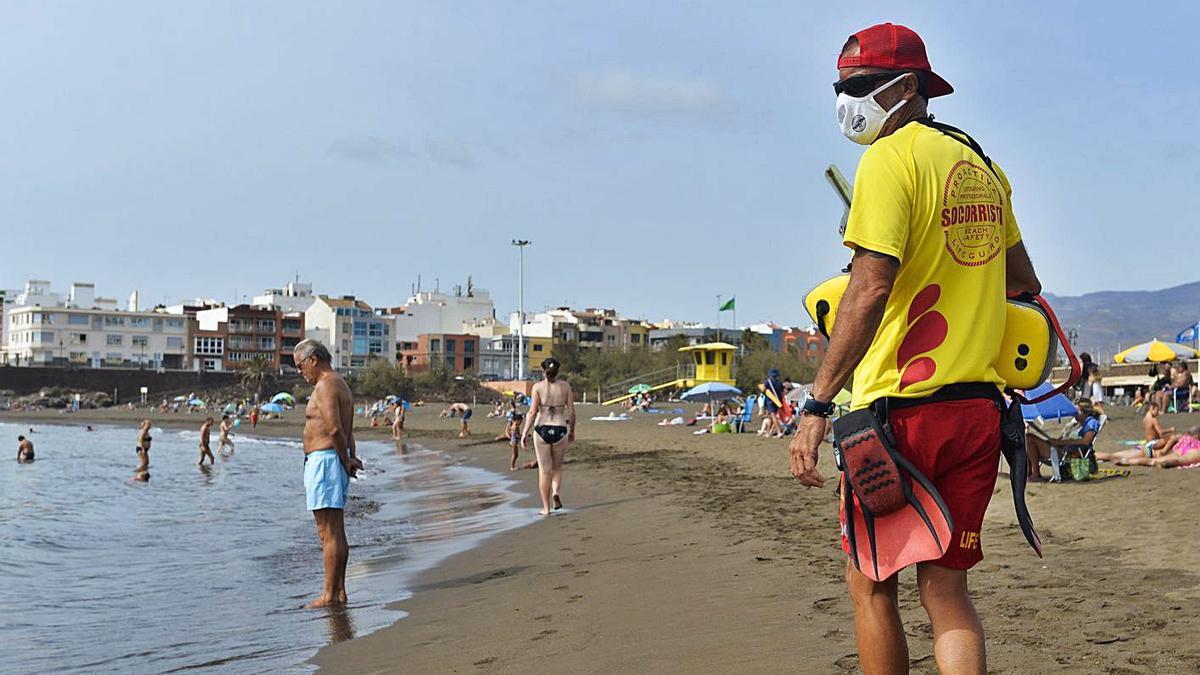 Grupos de personas disfrutan de un día de playa en Melenara, Gran Canaria.