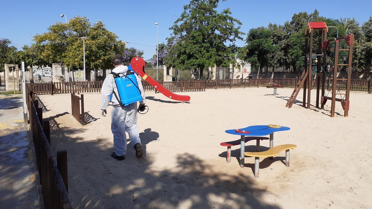 Un operario limpia una zona de juegos infantiles de Palma.