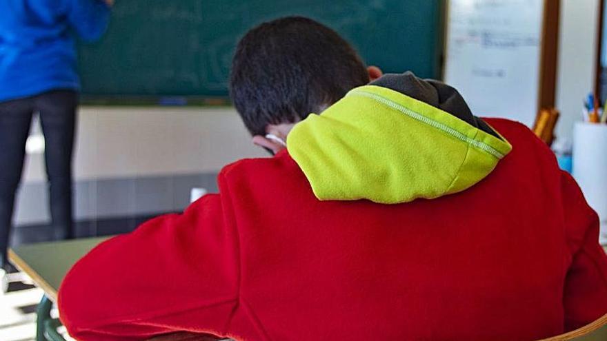 Un escolar toma nota durante una clase. | PERALES IBORRA