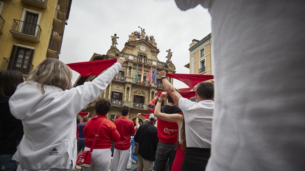 Un grupo de personas se concentra sosteniendo pancartas durante el arranque de los 'No Sanfermines'.