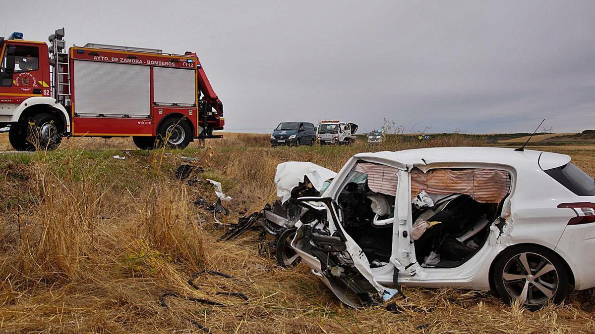 Uno de los vehículos siniestrados con los bomberos y otros medios, al fondo, en el accidente ocurrido ayer en Torres del Carrizal.   José Luis Fernández