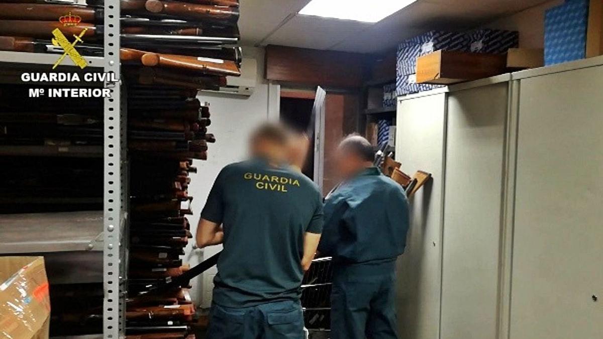 Dos guardia civiles manejan varias armas confiscadas.     // L. O.