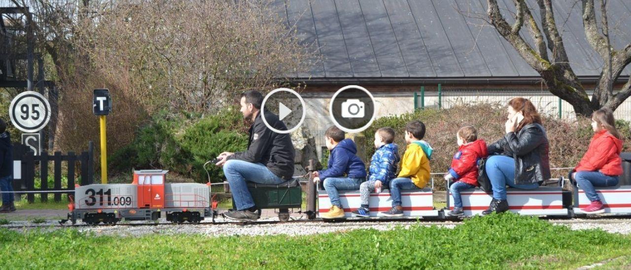Niños y adultos circulando en uno de los trenes del parque ferroviario.