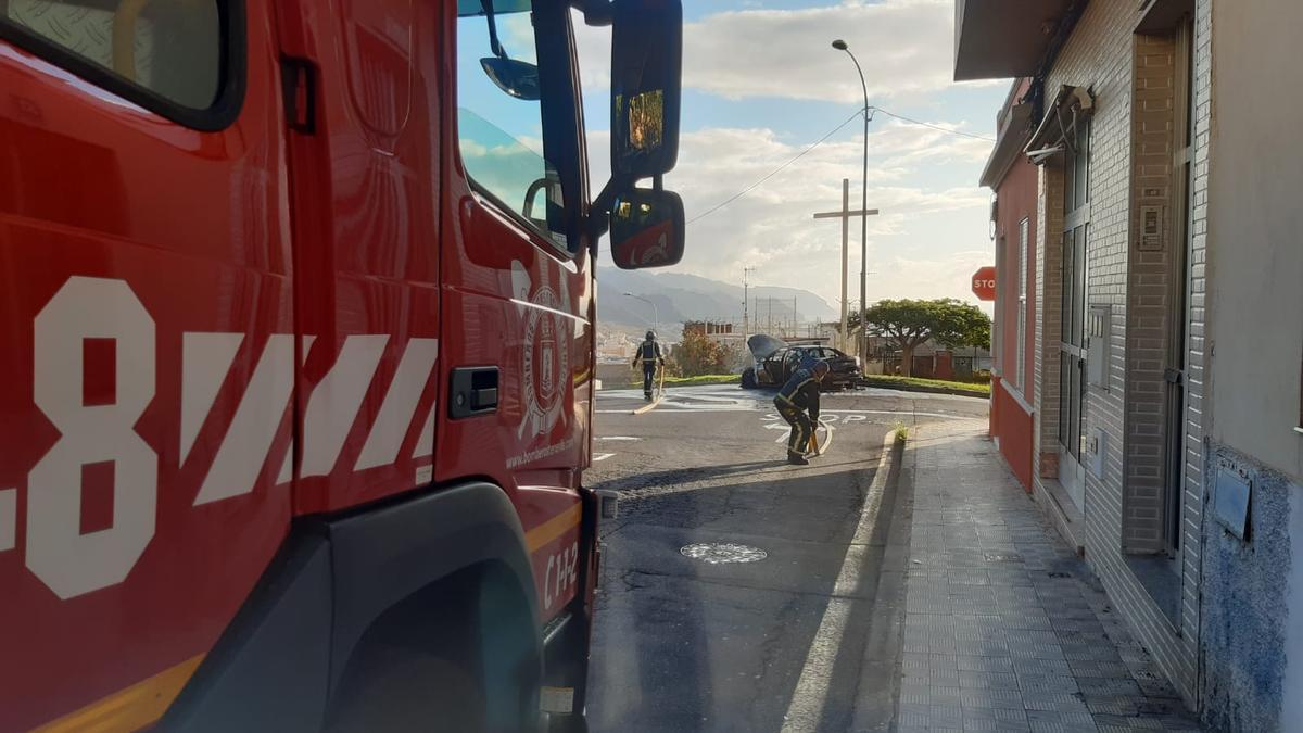 Los bomberos trabajan en la extinción de un incendio en un coche en el Camino del Hierro.