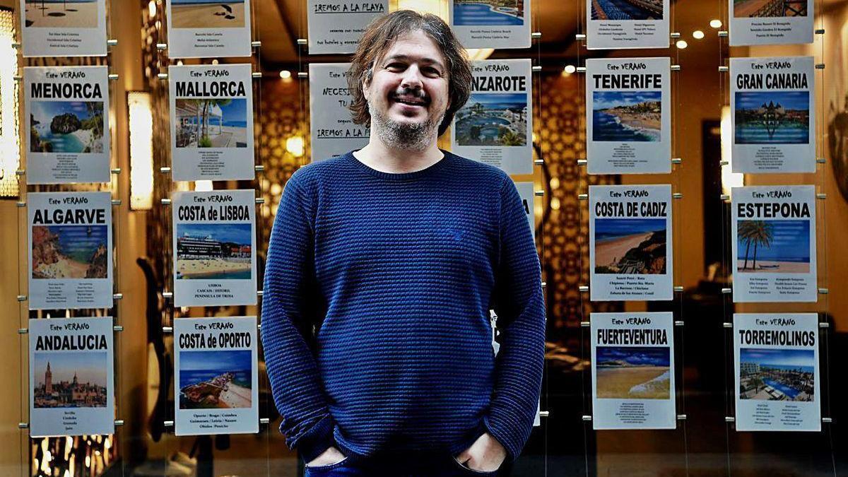Adolfo Díaz delante de ofertas de viajes de su agencia, Atlantis Travel Galera.