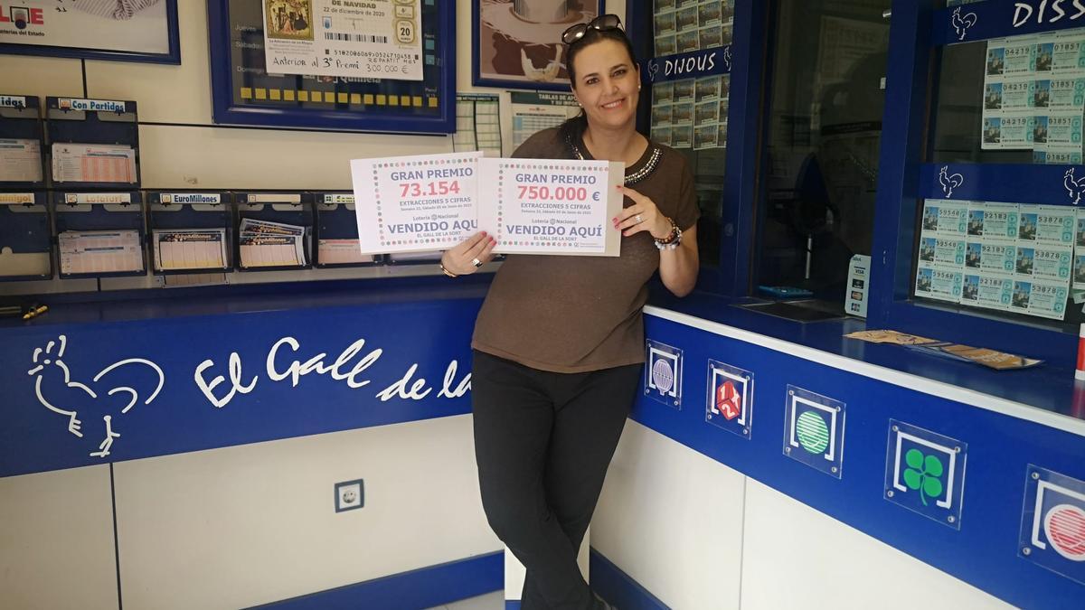 Anna Ballester, propietària d'El Gall de la Sort de Porqueres, mostrant el número guanyador i el premi.