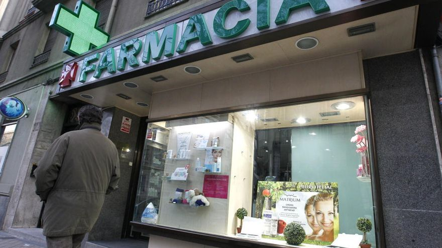 Un hombre camina frente a una farmacia