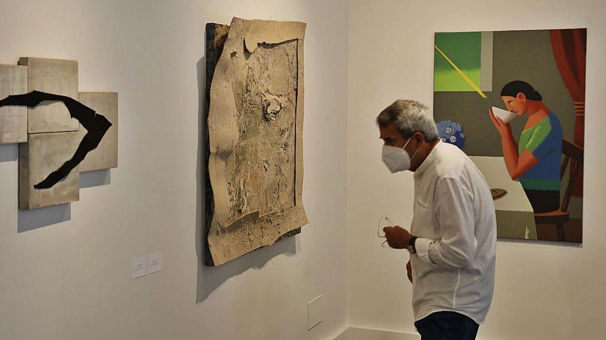 Santamarina, uno de los artistas participantes en la muestra, viendo algunas de las obras de sus compañeros.  | ÁNGEL GONZÁLEZ