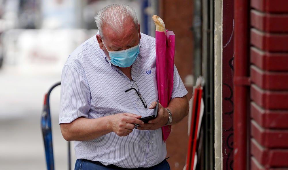 MADRID. 10.08.2020. CORONAVIRUS  COVID-19. Un hombre con unas barras de pan camina por la calle con mascarilla. FOTO: JOSÉ LUIS ROCA