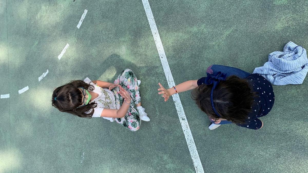 Dos niñas juegan en el parque de un colegio