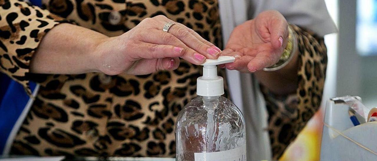 Una mujer desinfectándose las manos con gel.