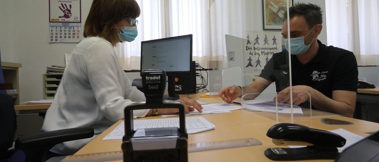 Una funcionaria registra un documento en una imagen de archivo
