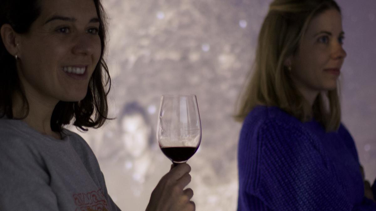 Pla mig d'una dona amb una copa de vi a la mà durant un fragment del mapatge interactiu i immersiu 'Vívid insòlit'. Imatge cedida a l'ACN el 14 de juny de 2021. (Horitzontal)