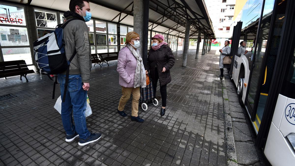 Personas esperando en la parada del autobús de la plaza de Galicia