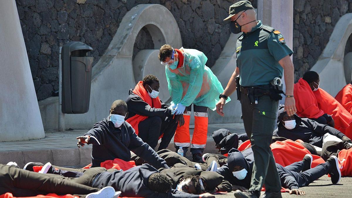 Subsaharianos llegados ayer al puerto de La Restinga, en El Hierro, atendidos por personal de Cruz Roja y Guardia Civil.