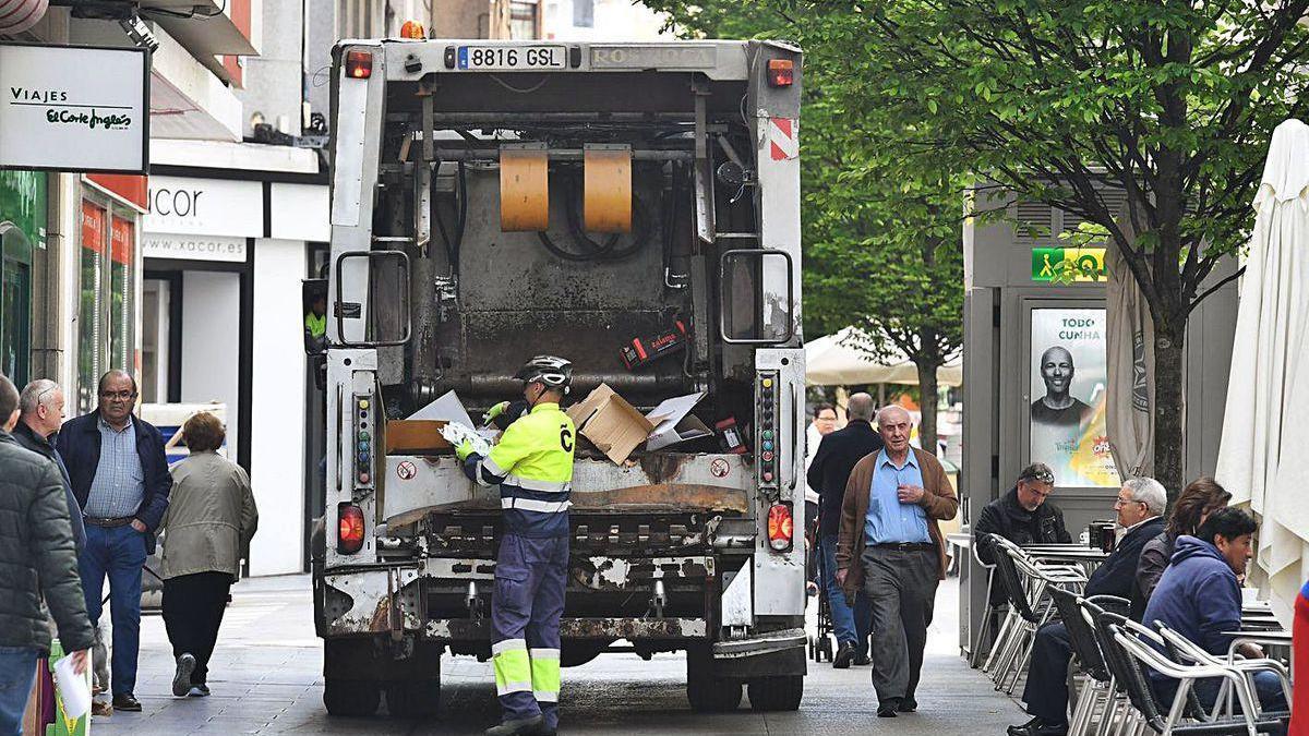 Un camión de la recogida de la basura retira cartón de los comercios en el centro.