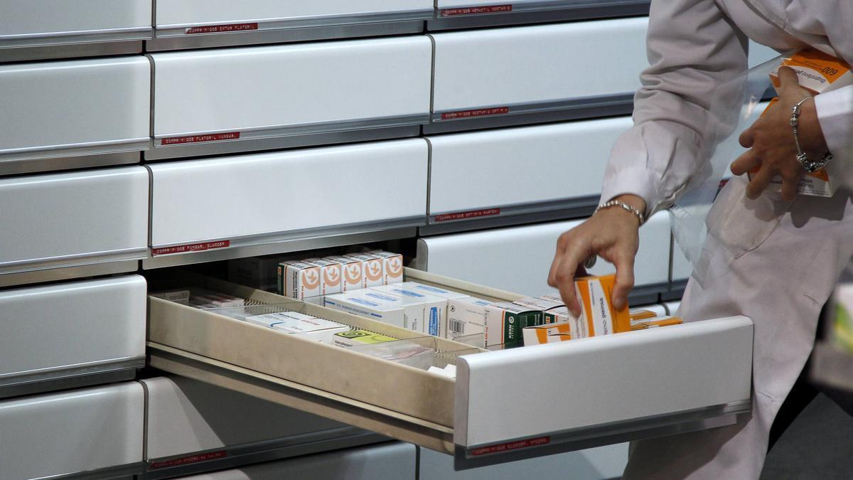 Una farmacéutica organiza medicamentos en su establecimiento.