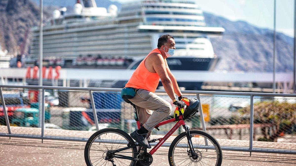 Un hombre pasea con su bicicleta por Santa Cruz.