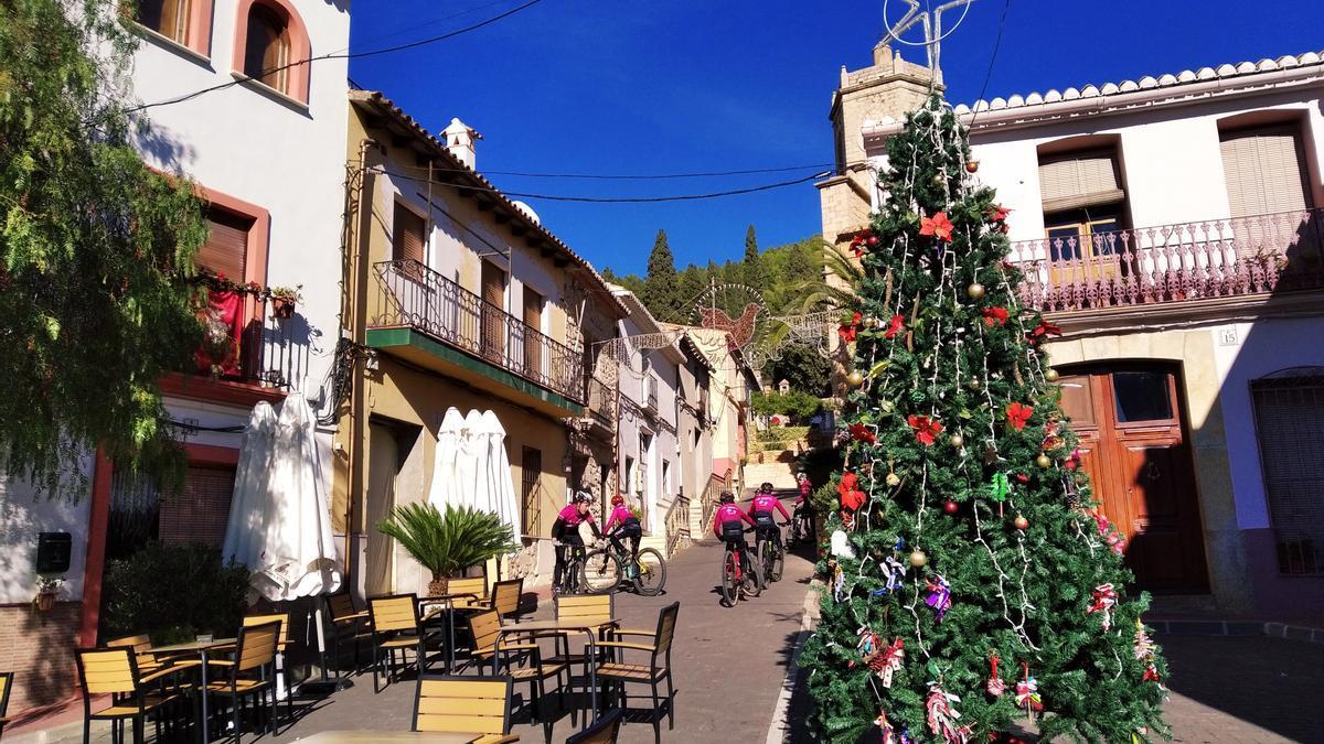 El árbol de Navidad en la plaza de Llíber, parada de ciclistas