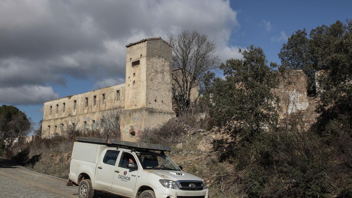 Un vehículo pasa por delante de las antiguas construcciones de la mina de Valdeflores.