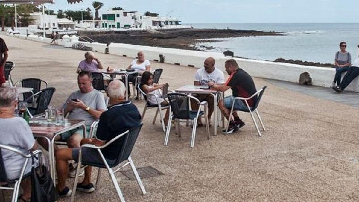 Tiuristas en una terraza junto al mar en la isla de Lanzarote.