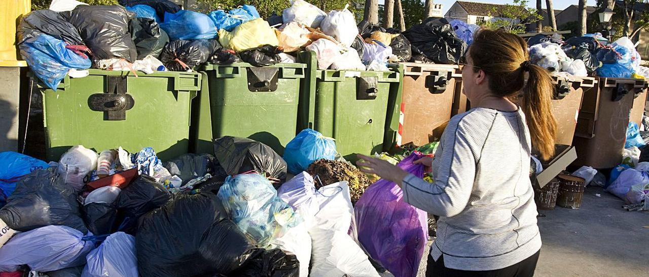 Una mujer deposita una bolsa de basura ante unos contenedores llenos.
