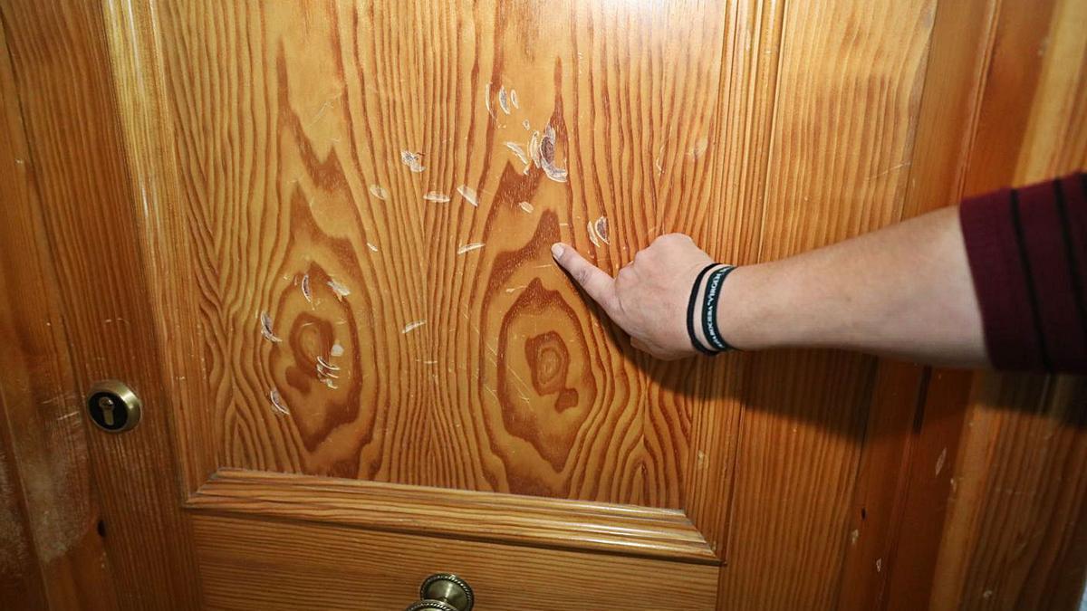 Una de las puertas que los residentes aseguran que ha destrozado su vecina a golpes.